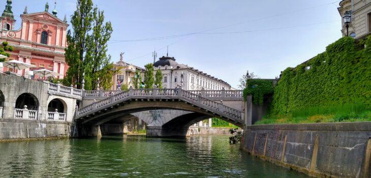 Das Bild zeigt die berühmten drei Brücken, aufgenommen von einem Boot auf der Ljubljanica